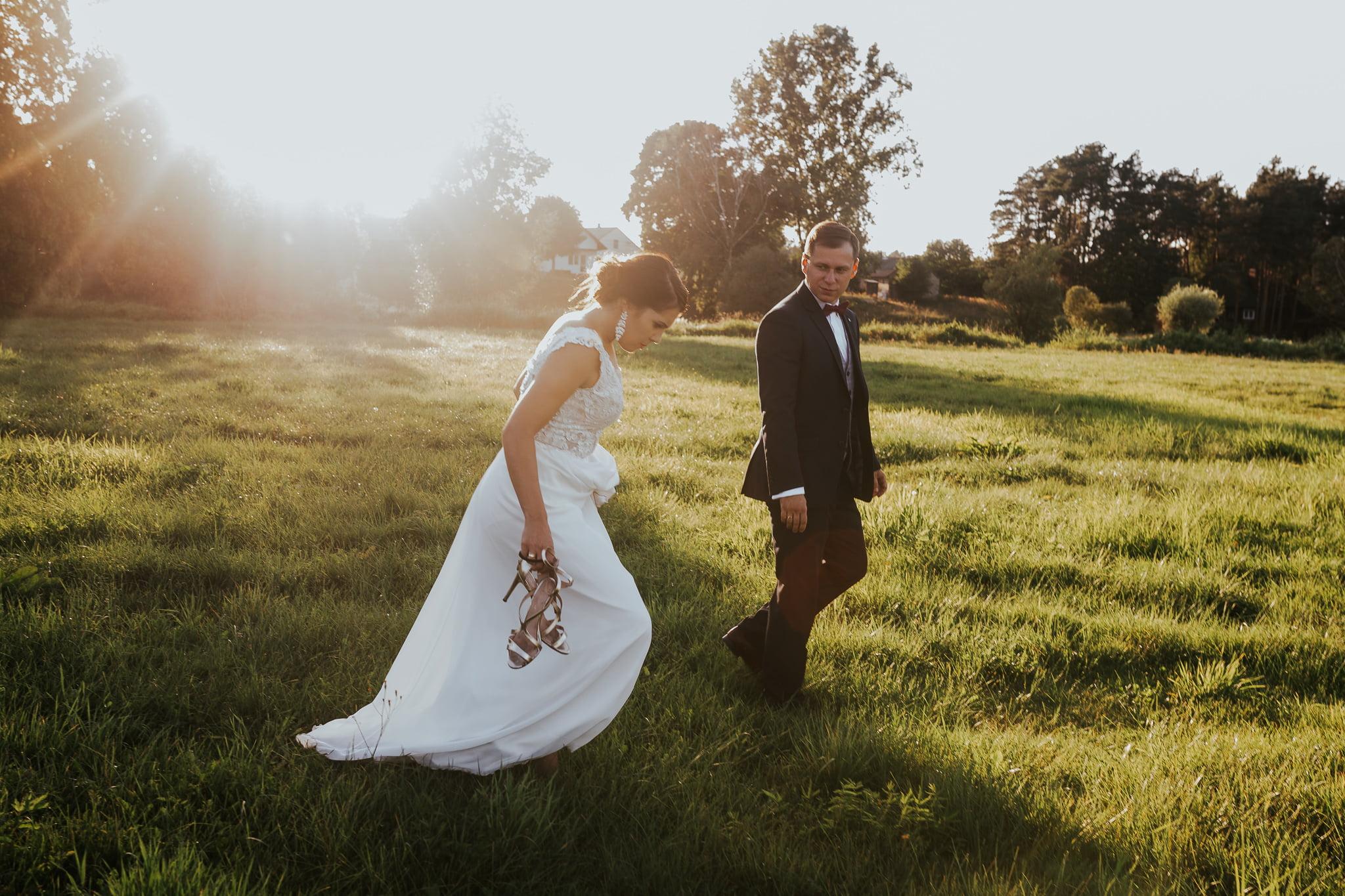 Panna Młoda i Pan Młody podczas sesji plenerowej na polu podczas zachodu słońca.